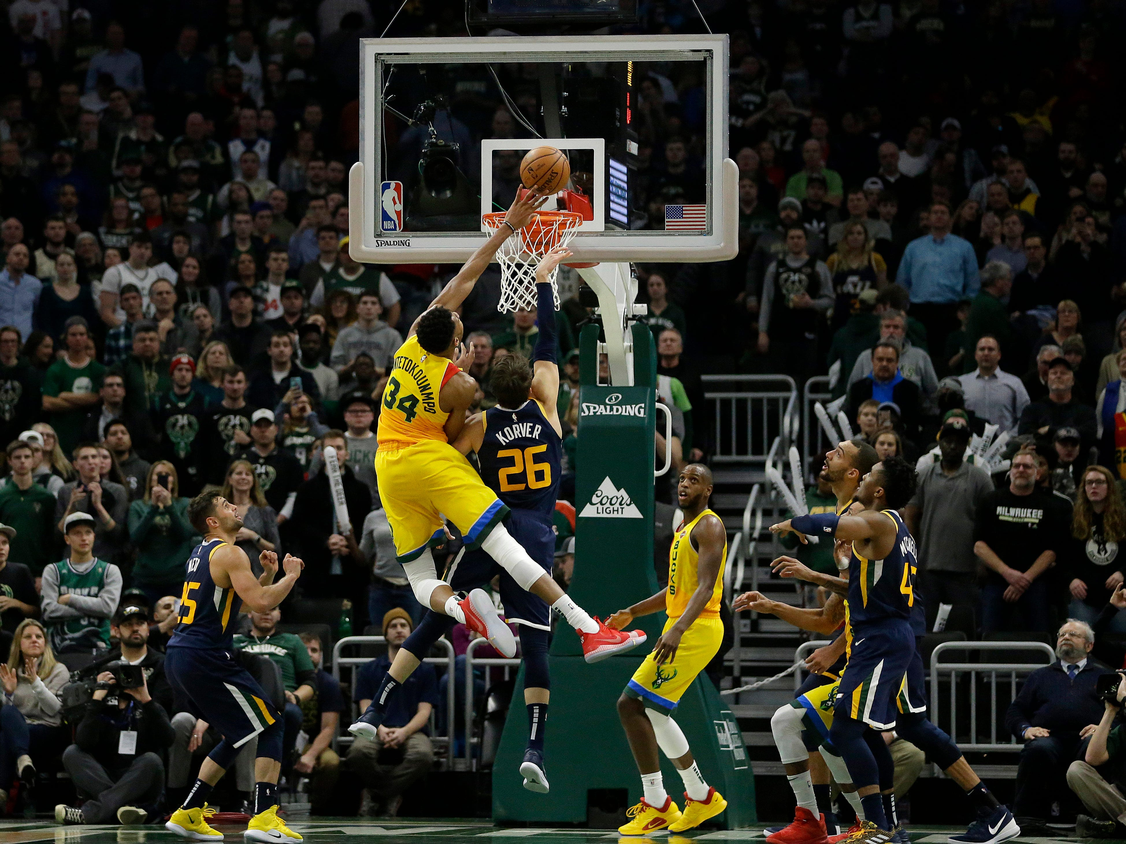 Giannis Antetokounmpo of the Bucks tips in a shot over the Jazz's Kyle Korver during the second half Monday.