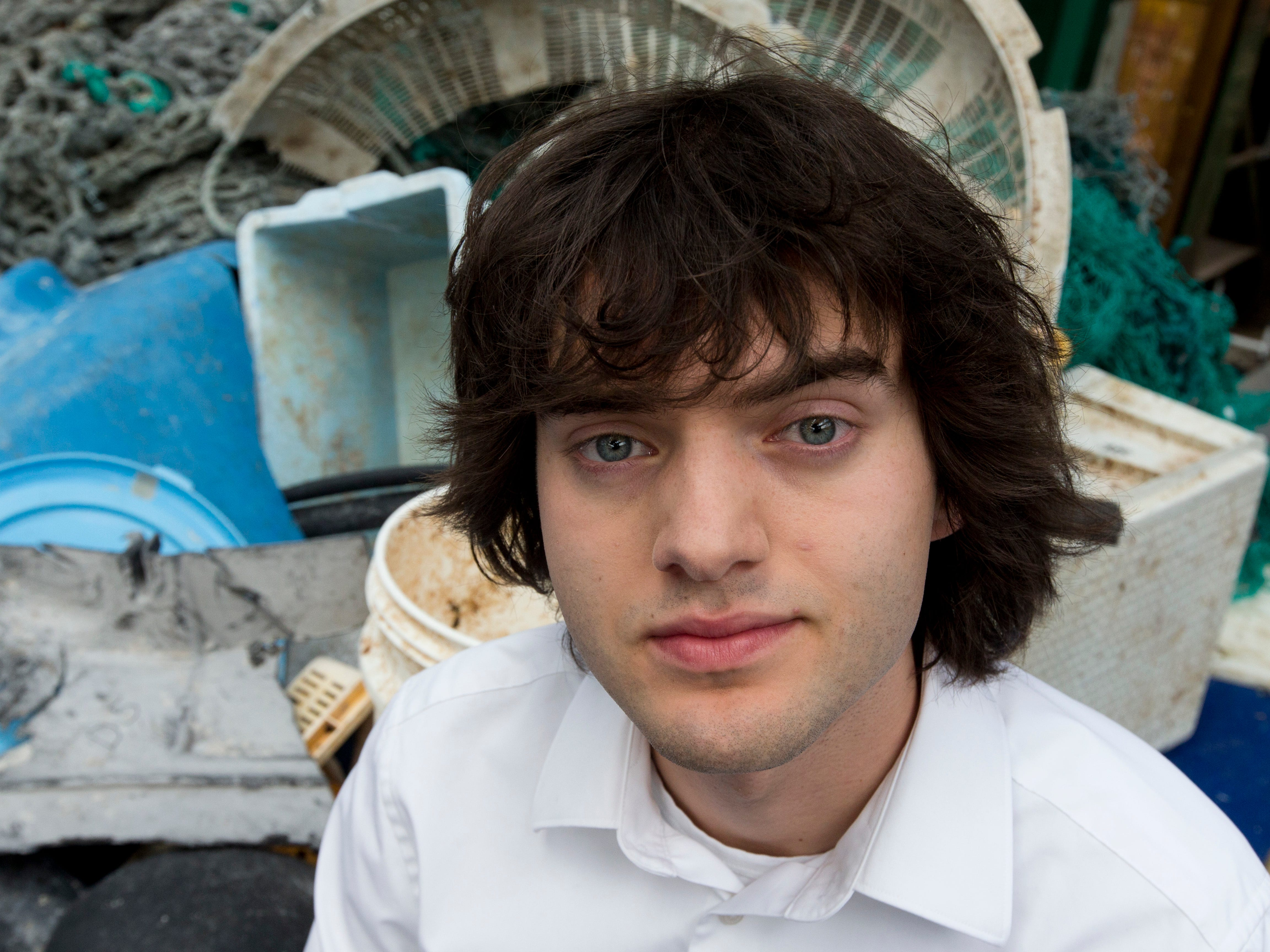 Dutch innovator Boyan Slat poses for a portrait in 2017 next to a pile of plastic garbage in Utrecht, Netherlands. Slat launched the Pacific Ocean cleanup project, including the floating boom that traveled to the Pacific garbage patch.