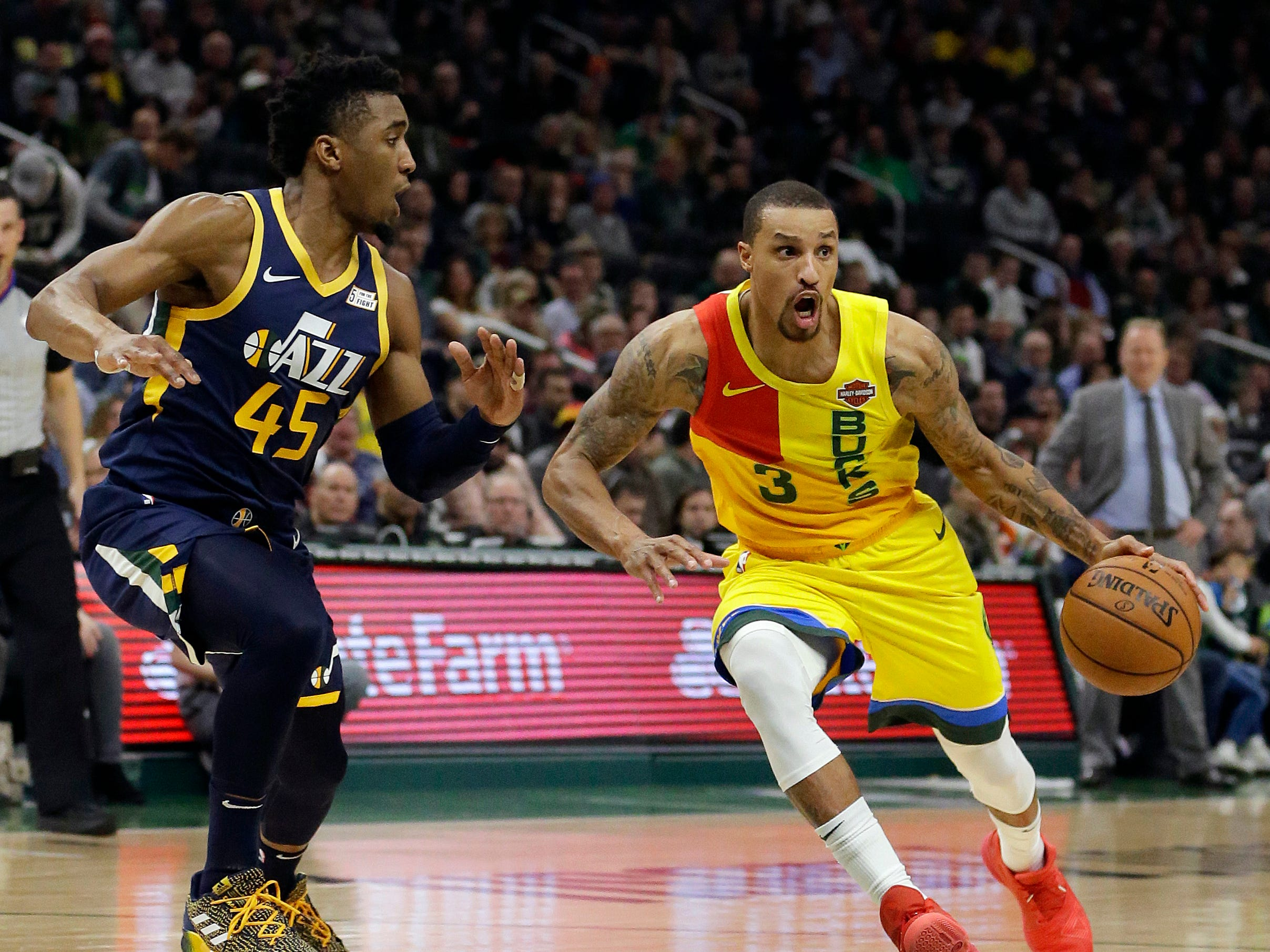 George Hill of the Bucks drives into the lane while being guarded by Donovan Mitchell of Utah on Monday night.