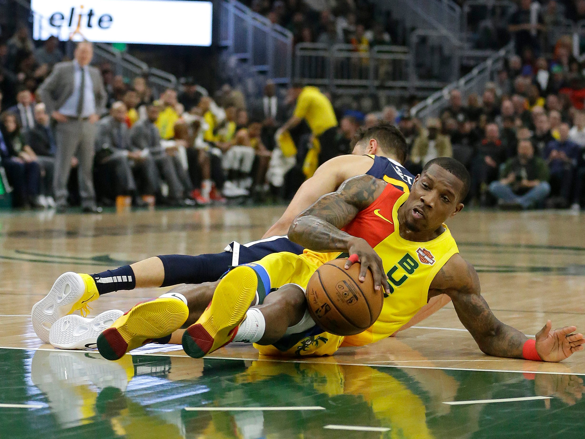 Eric Bledsoe of the Bucks beats Raul Neto of the Jazz to a loose ball during the first half Monday.