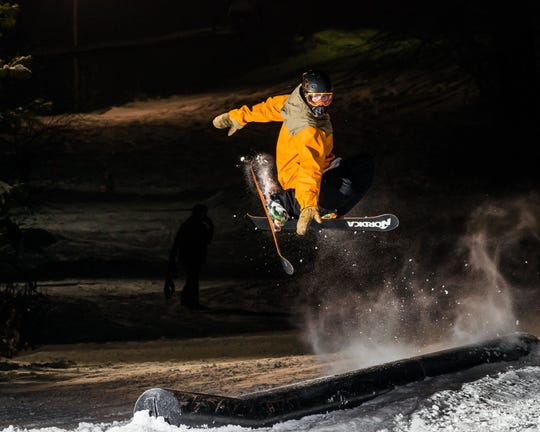 A skier does a trick above a terrain feature at Devil's Head Resort during a night-time outing.