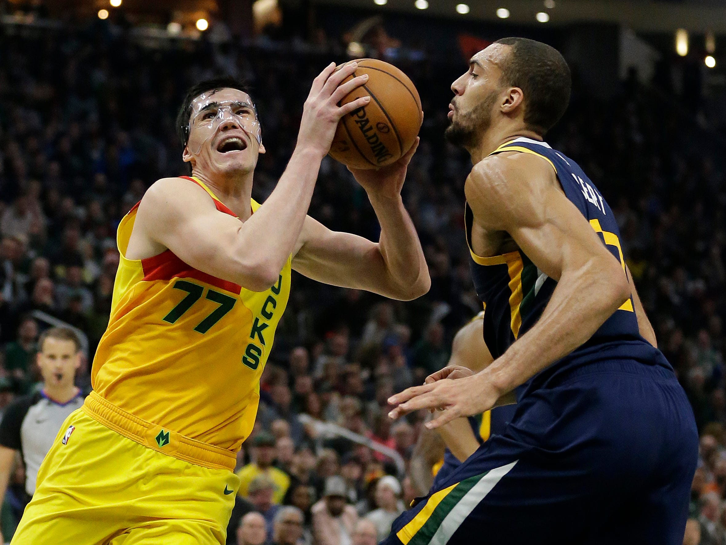 Masked-man Ersan Ilyasova of the Bucks drives against the Jazz's Rudy Gobert during the first half Monday.