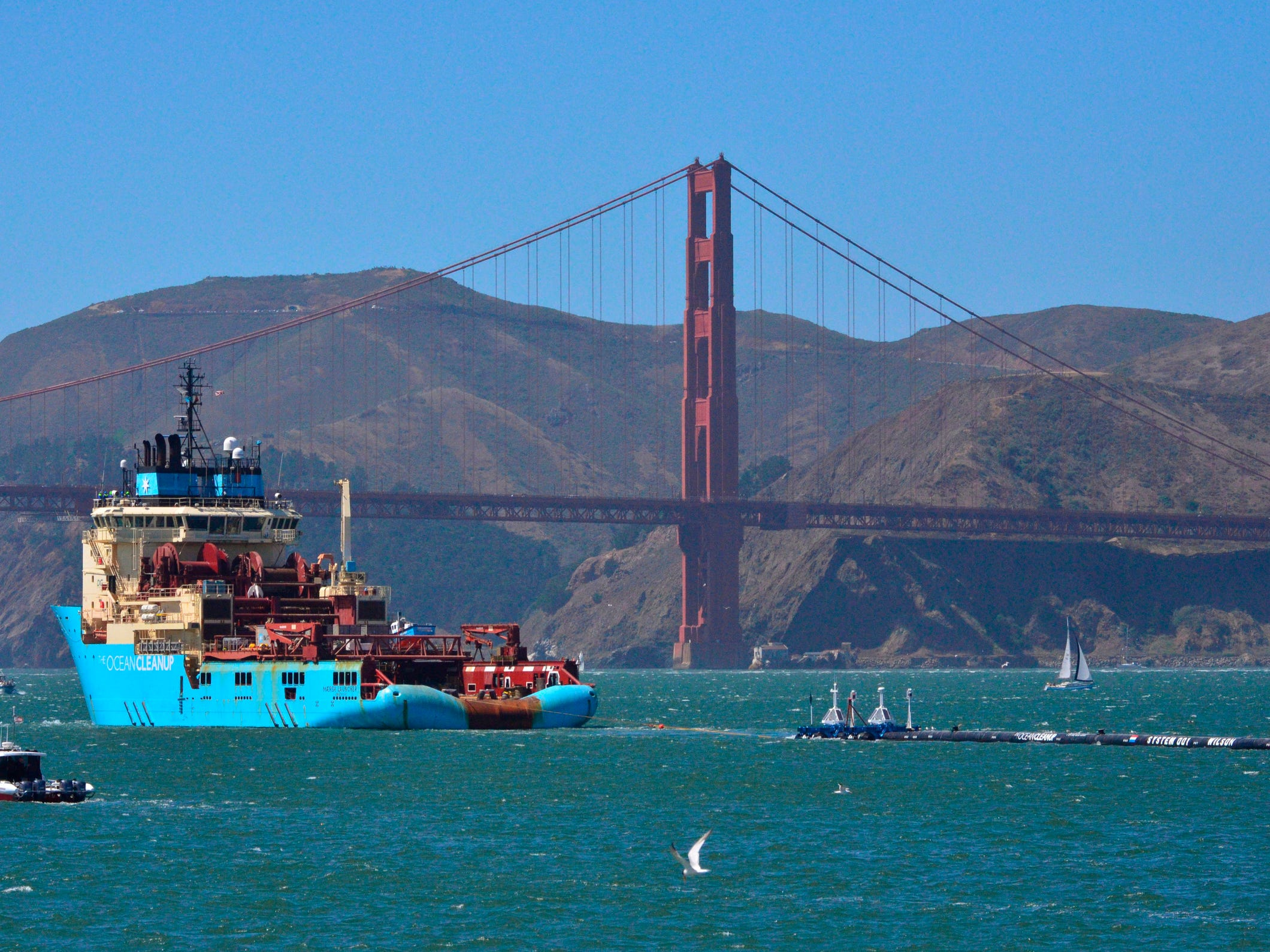 A ship tows The Ocean Cleanup's first buoyant trash-collecting device toward the Golden Gate Bridge in San Francisco en route to the Pacific Ocean in September 2018. Out in the Pacific, however, the boom broke apart under constant wind and waves. The break was discovered on Dec. 29, and the device was being towed back for repairs and overhaul. Boyan Slat, who launched the Pacific Ocean cleanup project, said he was disappointed, but not discouraged.