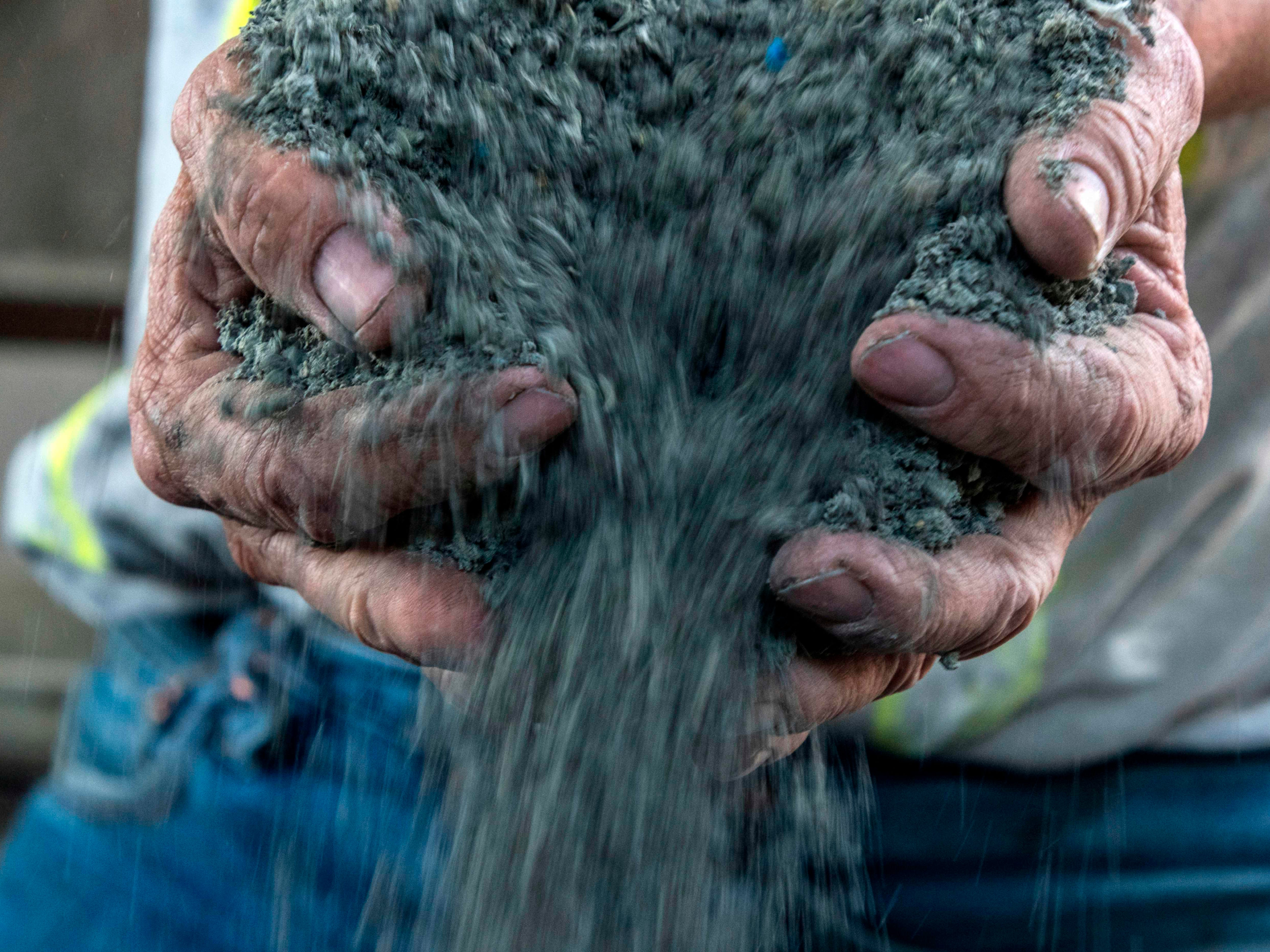 A man manipulates recycled plastic to make cement at an ecoblock factory in San Jose, Costa Rica, on Nov. 28, 2018. Even when plastics are recycled, uses for them can be hard to find.
