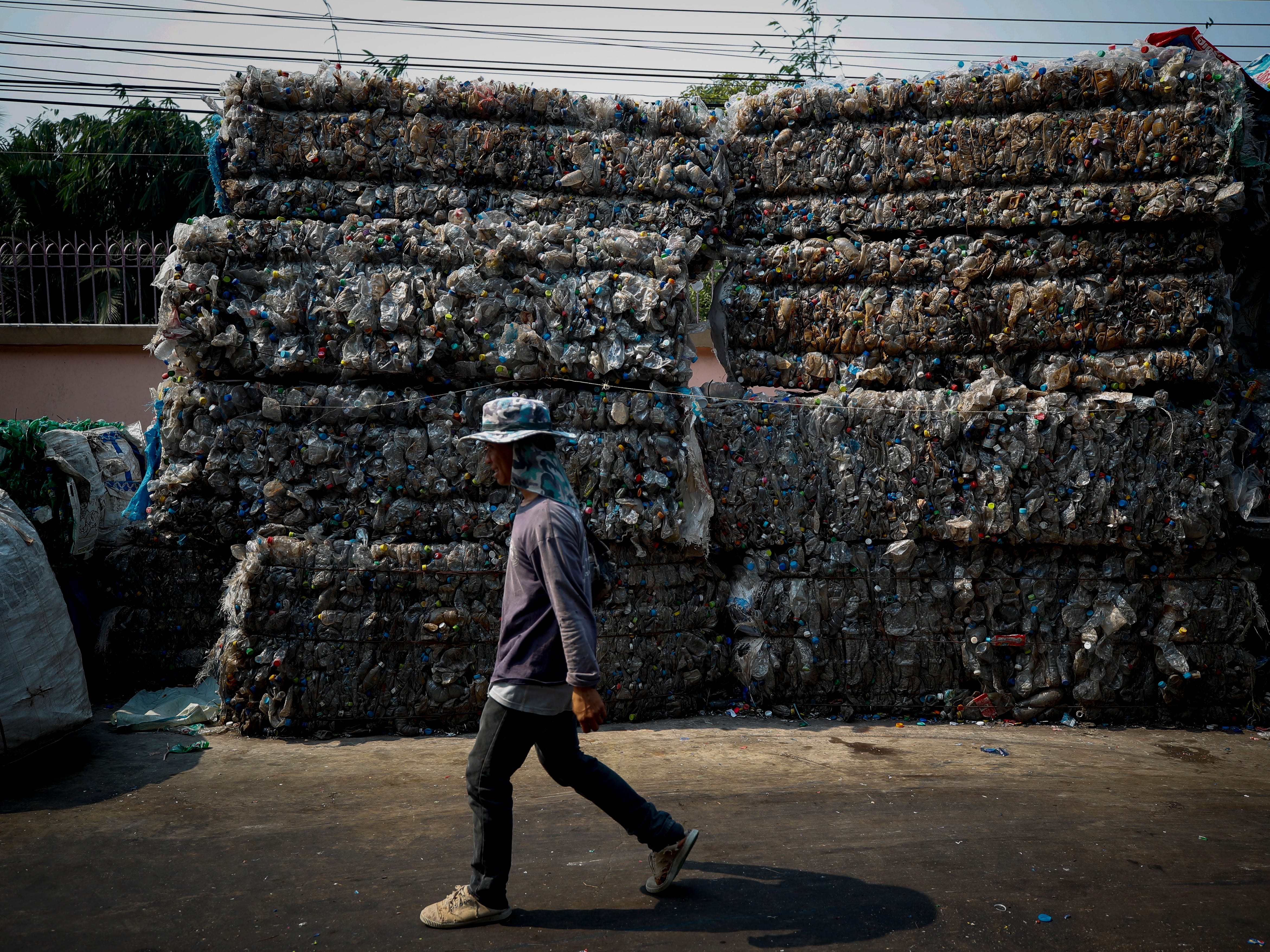 A migrant worker walks past pressed plastic bottles to be processed for recycling at a recycling plant near Bangkok, Thailand in December 2018.