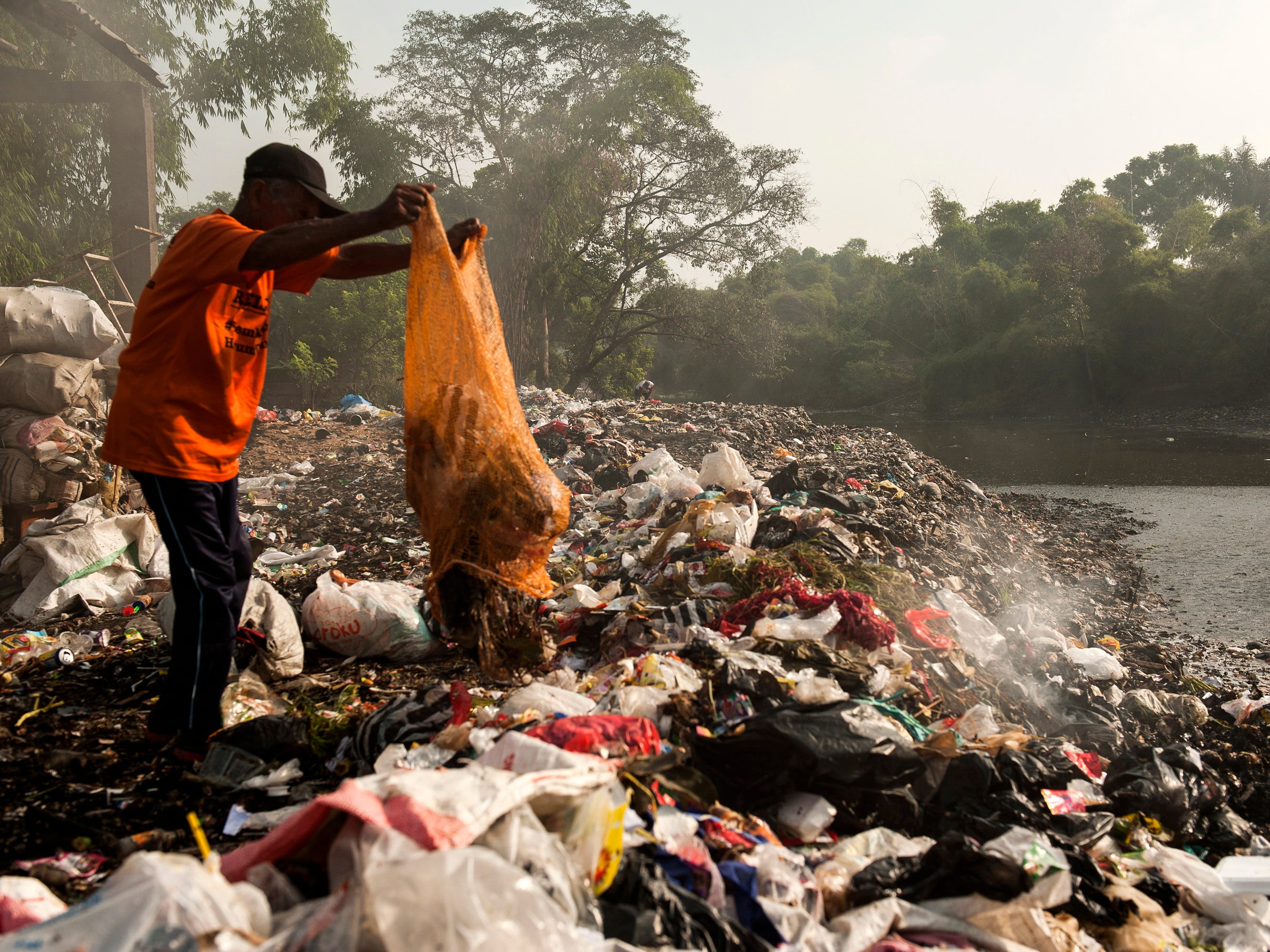 An Indonesian man sorts useable plastic waste on a polluted bank of the Citarum River in Bandung, Indonesia, in  January 2019.