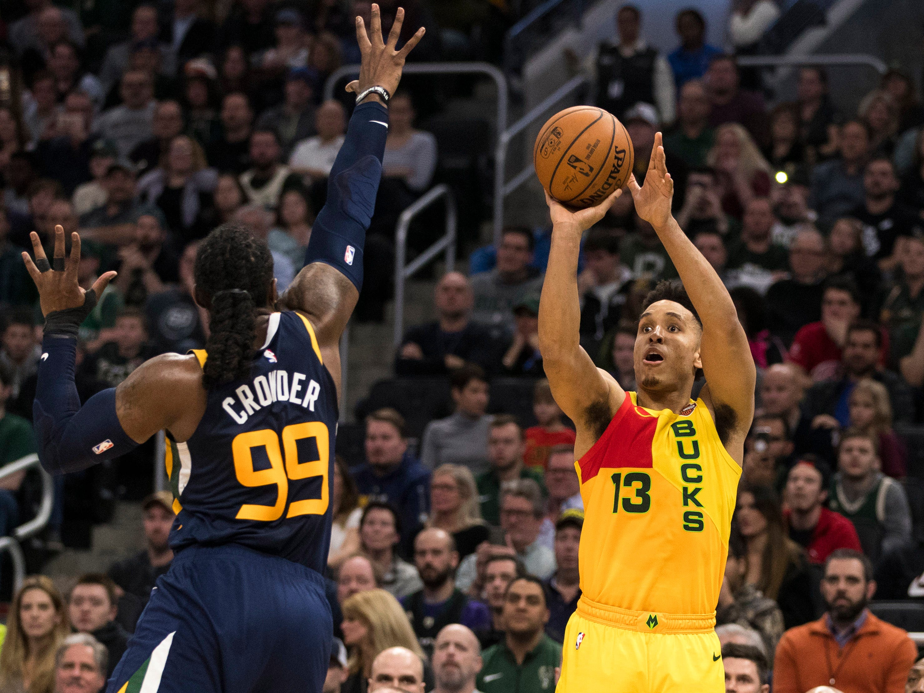 Bucks guard Malcolm Brogdon  launches a three-pointer over former Marquette standout Jae Crowder of the Jazz during the fourth quarter Monday.