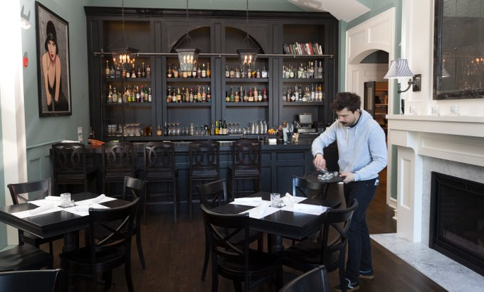 Daniel McNally sets tables Tuesday in the new dining room at Buckley's Restaurant and Bar, 801 N. Cass St. The restaurant, which expanded into the building to the north, opens to the public Wednesday.