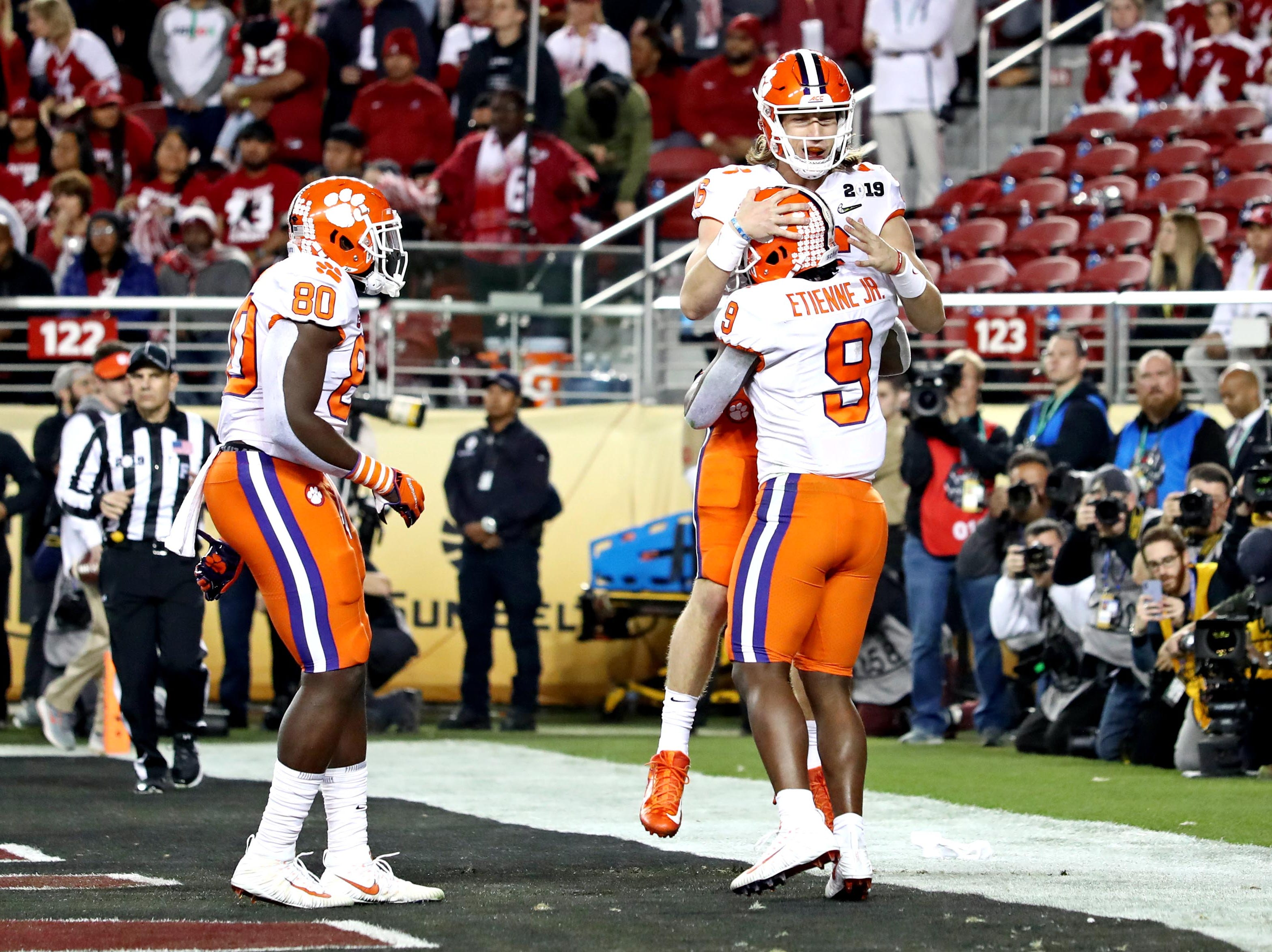 Jan 7, 2019; Santa Clara, CA, USA; Clemson Tigers running back Travis Etienne (9) celebrates with Clemson Tigers quarterback Trevor Lawrence (16) after a touchdown during the first half against the Alabama Crimson Tide during the 2019 College Football Playoff Championship game at Levi's Stadium. Mandatory Credit: Matthew Emmons-USA TODAY Sports