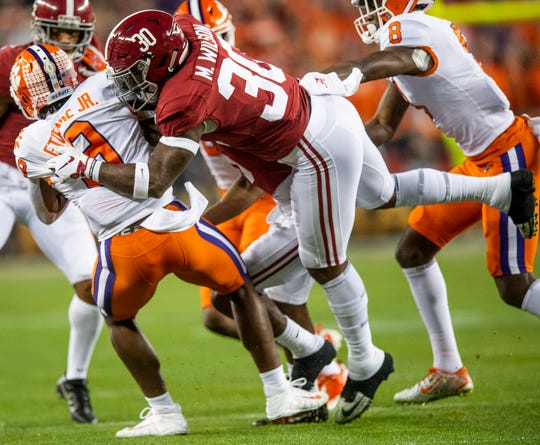 Alabama linebacker Mack Wilson (30) stops Clemson running back Travis Etienne (9) In first half action of the College Football Playoff National Championship game at Levi's Stadium in Santa Clara, Ca., on Monday January 7, 2019.