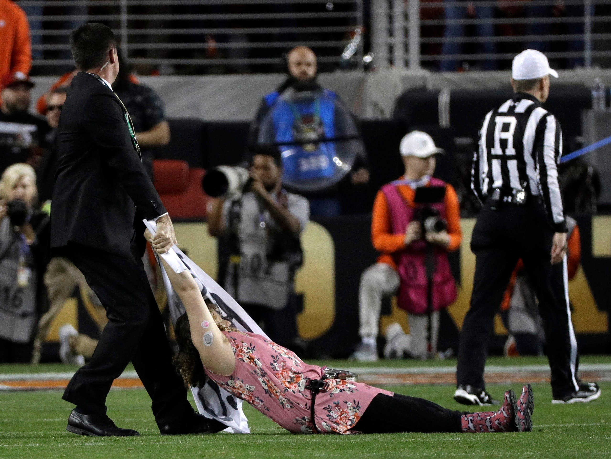 A fan is removed after running on the field during the first half the NCAA college football playoff championship game between Alabama and Clemson, Monday, Jan. 7, 2019, in Santa Clara, Calif. (AP Photo/David J. Phillip)