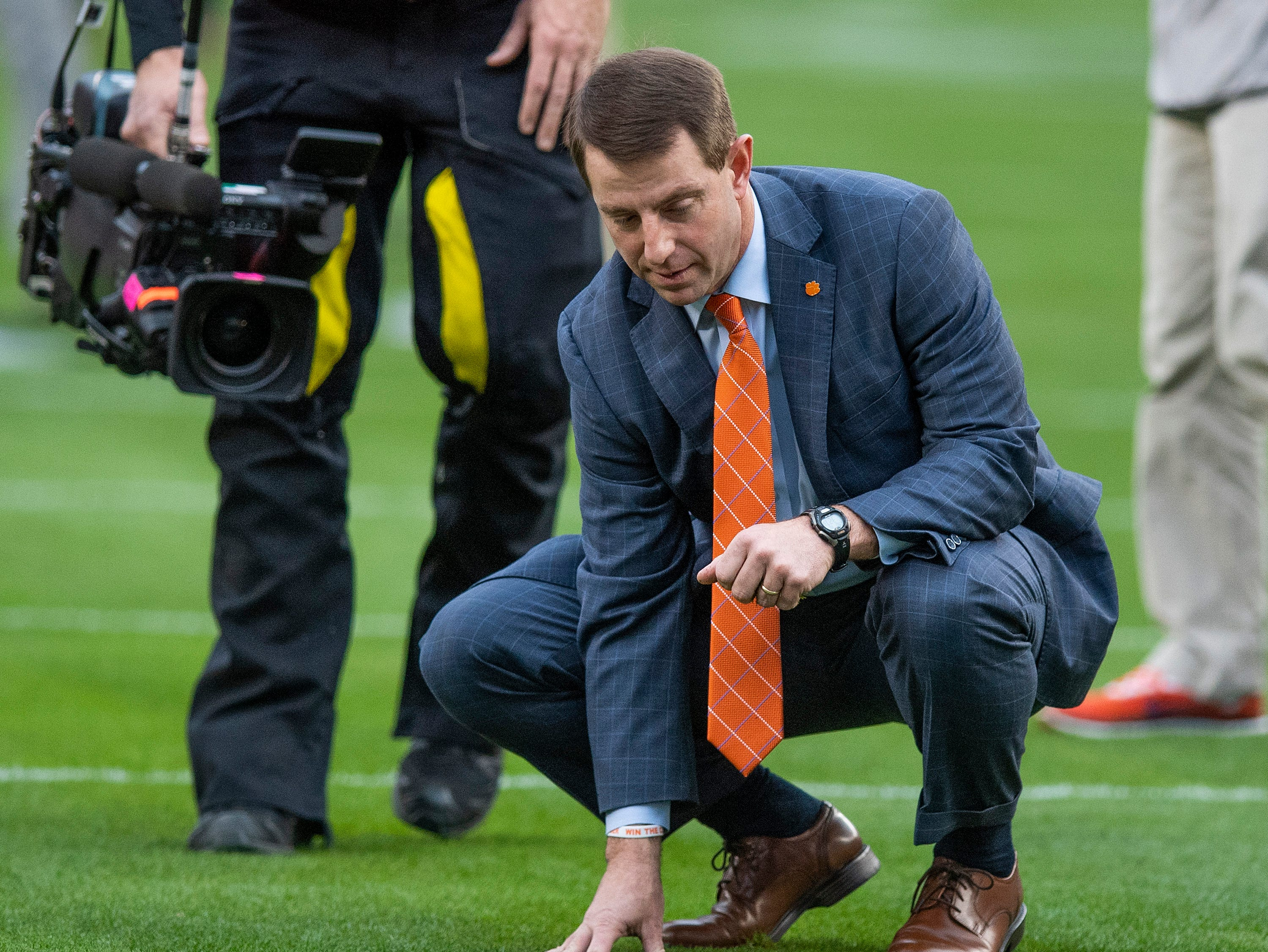Clemson head coach Dabo Swinney  checks the turf as he arrives with his team for the College Football Playoff National Championship game at Levi's Stadium in Santa Clara, Ca., on Monday January 7, 2019.