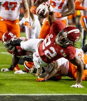 Alabama running back Najee Harris (22) stretches for the engine and comes up short against Clemson In first half action of the College Football Playoff National Championship game at Levi's Stadium in Santa Clara, Ca., on Monday January 7, 2019.
