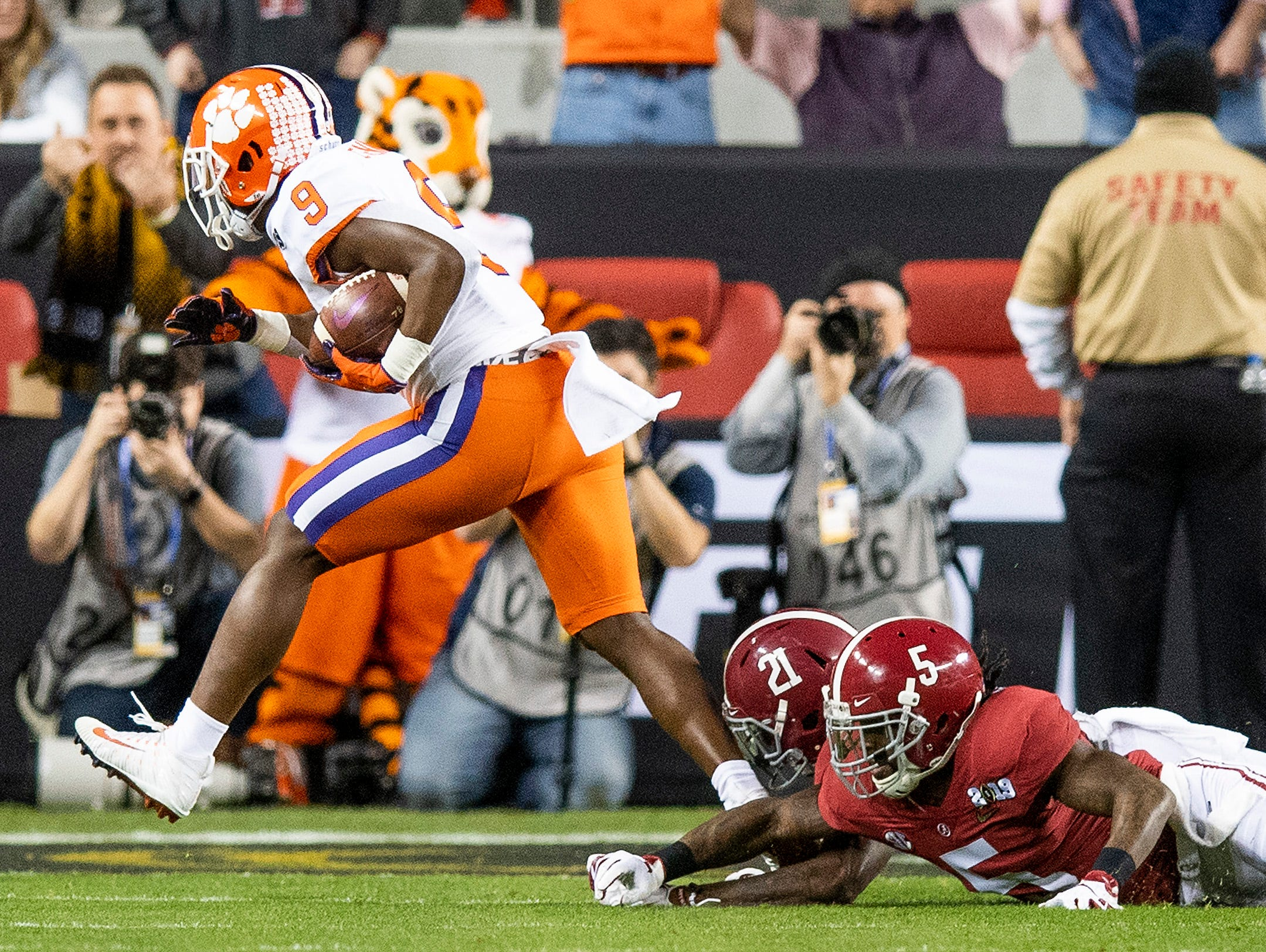 Clemson running back Travis Etienne (9)  gets away from Alabama defensive backs Shyheim Carter (5) and Jared Mayden (21) to score a touchdown in first half action of the College Football Playoff National Championship game at Levi's Stadium in Santa Clara, Ca., on Monday January 7, 2019.