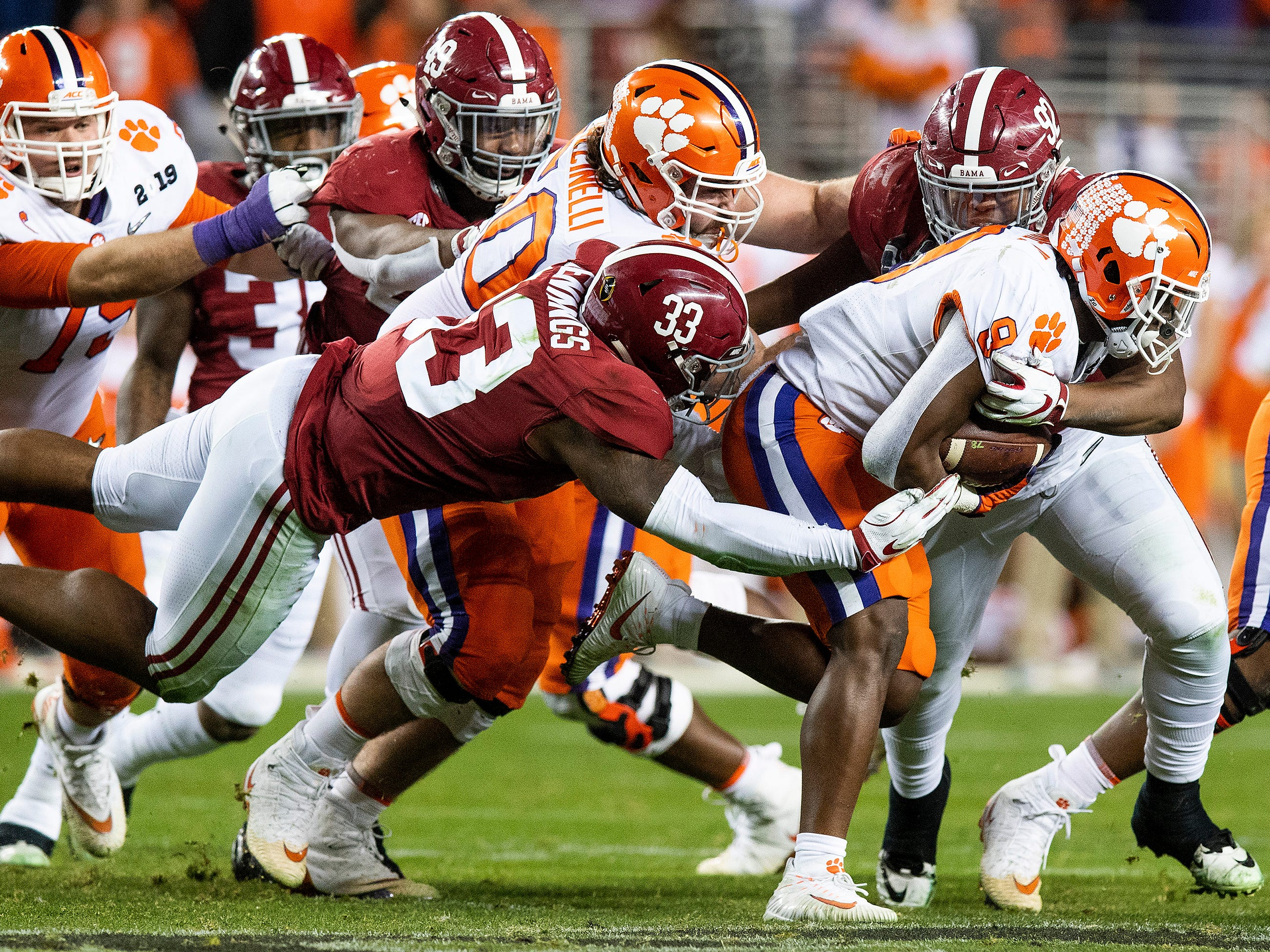Alabama linebacker Anfernee Jennings (33) and defensive lineman Quinnen Williams (92) stops Clemson running back Travis Etienne (9) In second half action of the College Football Playoff National Championship game at Levi's Stadium in Santa Clara, Ca., on Monday January 7, 2019.