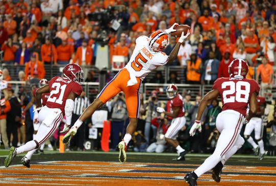 Jan 7, 2019; Santa Clara, CA, USA; Clemson Tigers wide receiver Tee Higgins (5) catches a touchdown pass between Alabama Crimson Tide defensive back Jared Mayden (21) and defensive back Josh Jobe (28) in the third quarter during the 2019 College Football Playoff Championship game at Levi's Stadium. Mandatory Credit: Mark Rebilas-USA TODAY Sports