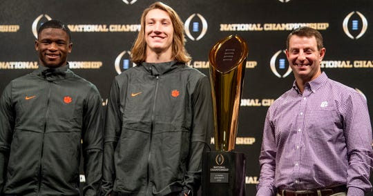Clemson cornerback Trayvon Mullen (1), quarterback Trevor Lawrence (16)  and head coach Dabo Swinney  pose with the National Championship Trophy during the College Football Playoff National Championship press conference in San Jose, Ca., on Tuesday January 8, 2019.