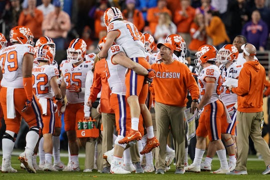 Jan 7, 2019; Santa Clara, CA, USA; Clemson Tigers quarterback Trevor Lawrence (16) is greeted defensive tackle Jordan Williams (59) and head coach Dabo Swinney during the fourth quarter in the 2019 College Football Playoff Championship game against the Alabama Crimson Tide at Levi's Stadium. Mandatory Credit: Kyle Terada-USA TODAY Sports