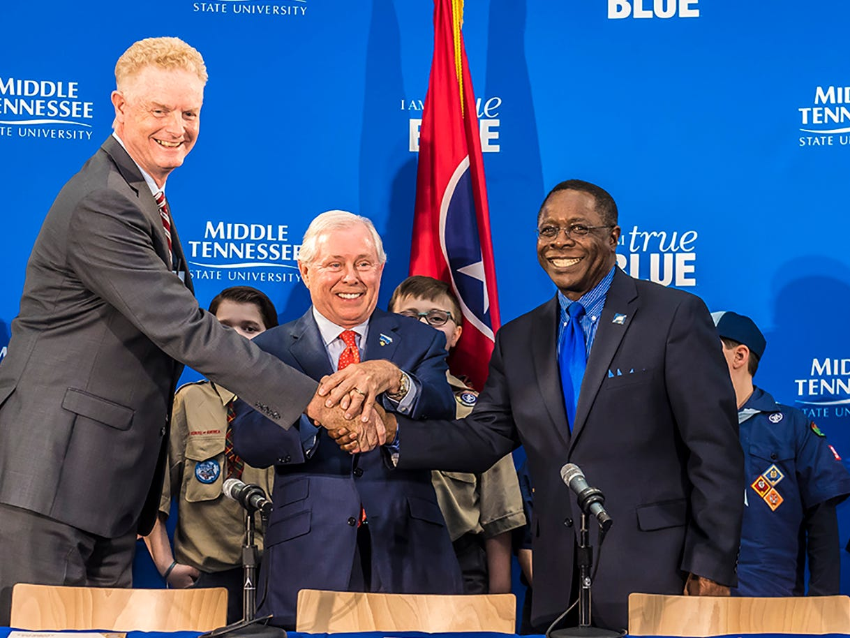 From right to left, MTSU President Sidney A. McPhee, MTSU Trustee J.B. Baker, and Larry Brown, CEO of the Middle Tennessee Council of the Boy Scouts of America, shake hands after signing a partnership Wednesday, March 7, in the Strobel Lobby at MTSU.   An MTSU grad, Baker is CEO and owner of Sprint Logistics