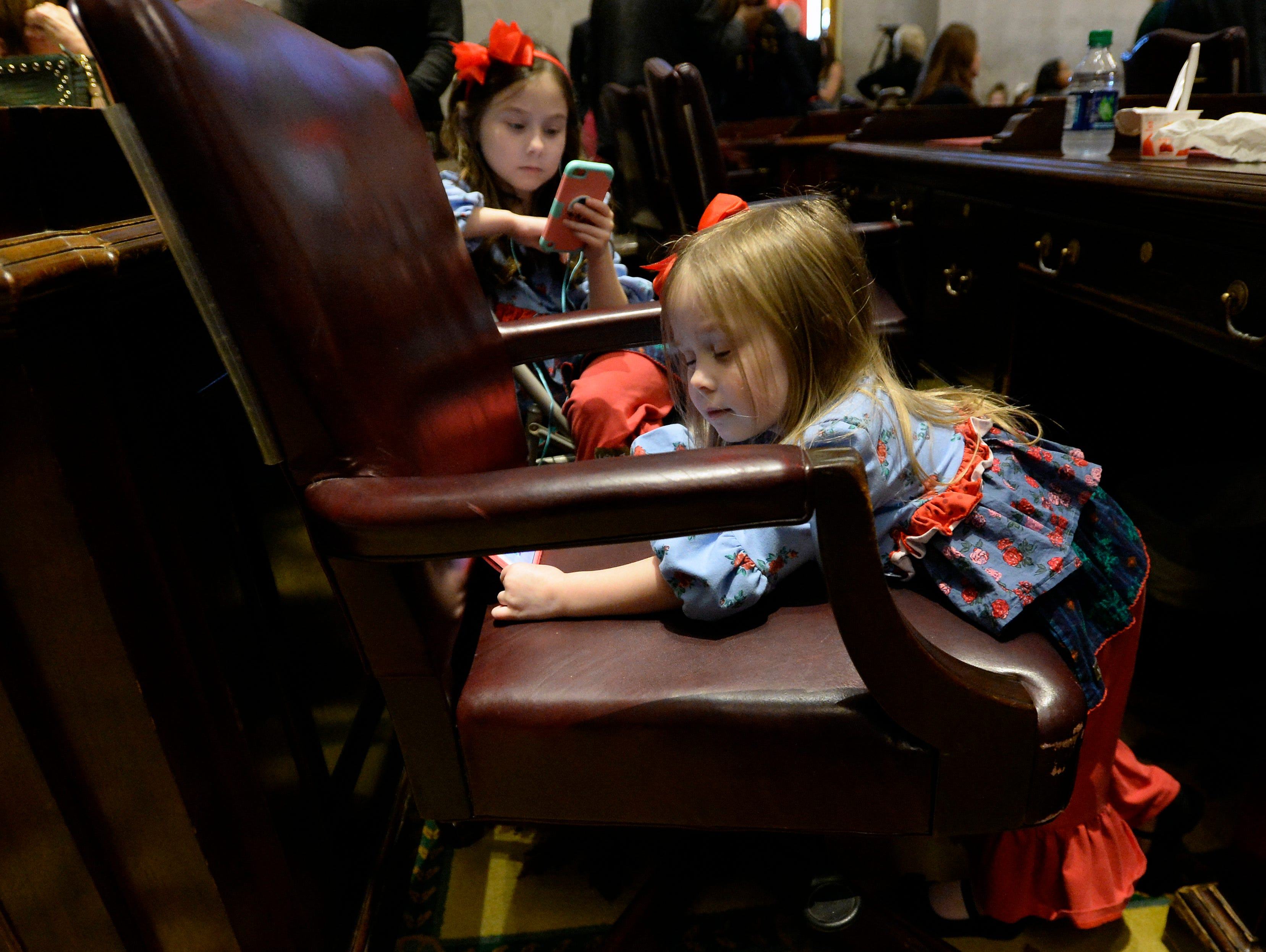 Madelyn Hicks, 3, daughter of legislative member, Gary Hick, plays with her cell phone  before the start of the House of Representatives opening day of the 111th General Assembly on Tuesday, Jan. 8, 2019, in Nashville, Tenn.