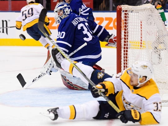 Toronto Maple Leafs goaltender Michael Hutchinson (30) makes a save as Nashville Predators right wing Viktor Arvidsson (33) looks for the puck during third-period NHL hockey game action in Toronto, Monday, Jan. 7, 2019.