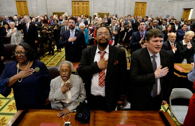 Legislative members stand with their families as they recite the pledge of allegiance during the House of Representatives opening day of the 111th General Assembly on Tuesday in Nashville.