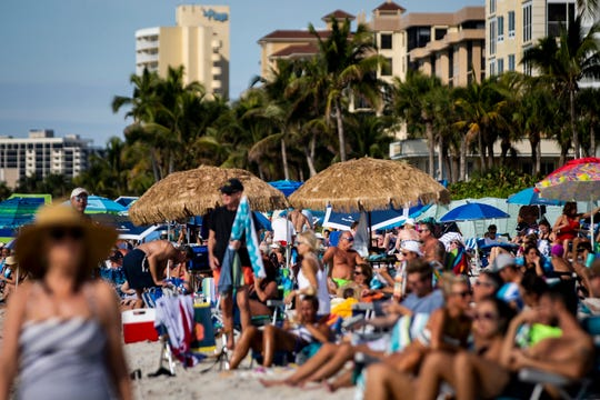 Beachgoers fill the crowded public access area on Tuesday, Jan. 8, 2019, at Vanderbilt Beach in North Naples.