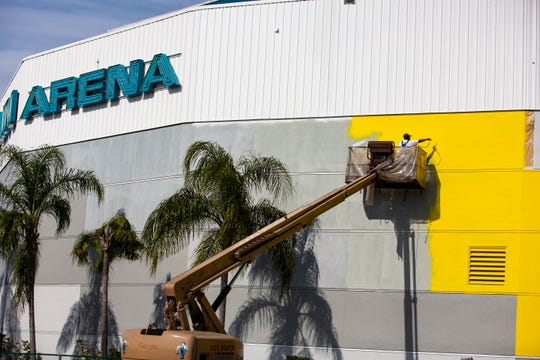 Workers from Vic's Painting & Reconstruction of Fort Myers have been working for three weeks on painting the Hertz Arena in Estero, yellow, as on Jan. 8, 2018. The  Estero-based rental car giant took over the naming rights of the Germain Arena last year.