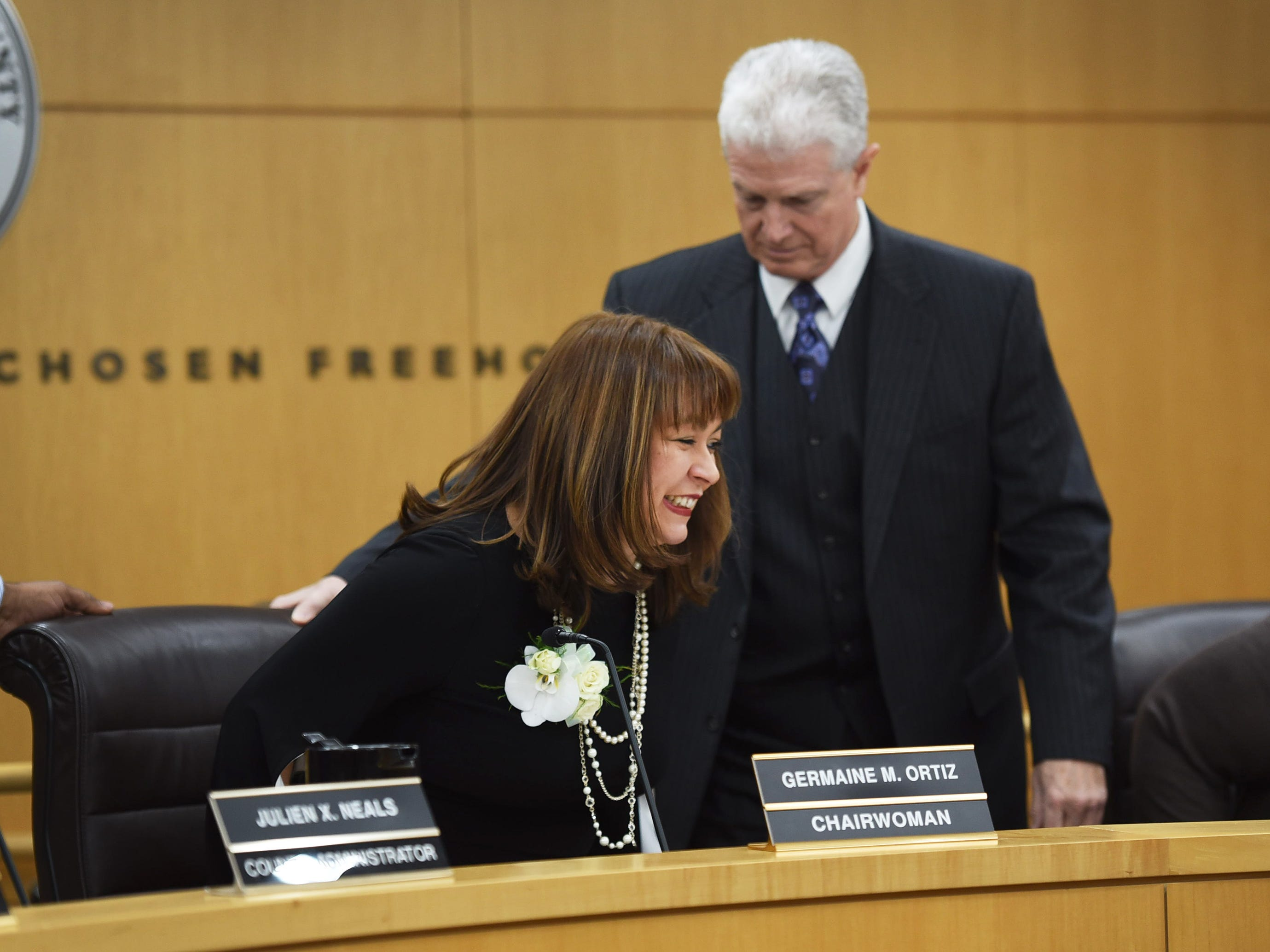 Germaine Ortiz is escorted by Edward Florio, Freeholder Counsel to be seated in the chair of Chairwoman after being sworn in as a Chairwoman by Senator Bob Menendez (not shown) during the annual Bergen County freeholder board's reorganization meeting at Bergen County Plaza in Hackensack on 01/07/19.