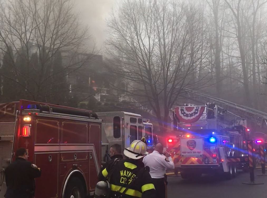 Firefighters battle a three-alarm blaze at a mansion in Wayne on Tuesday, Jan. 8, 2019.