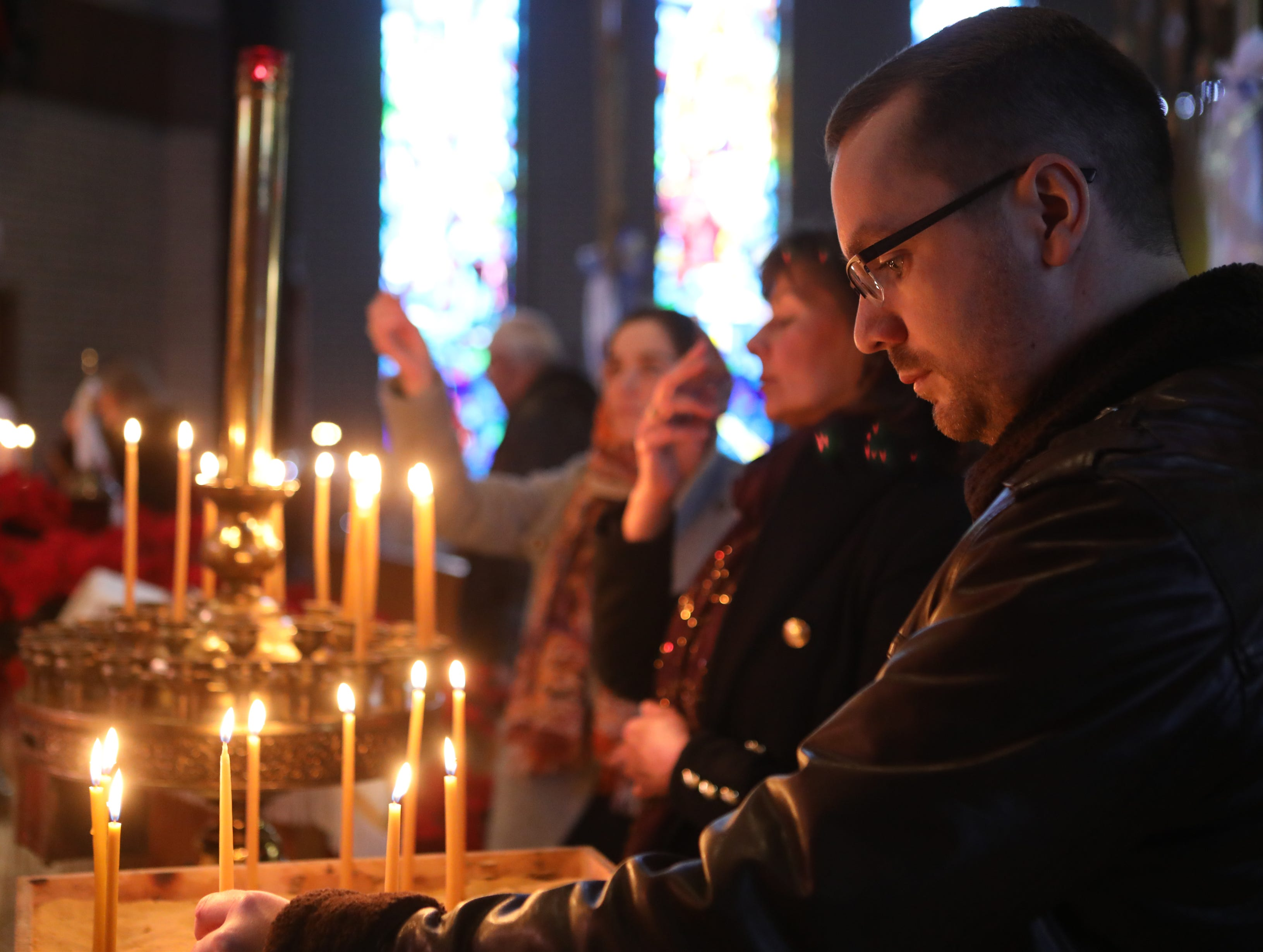 Iurii Baiurak, of Rutherford, lights a memorial candle at the Ukrainian Orthodox Holy Ascension Church, in Clifton. Monday, January 7, 2019