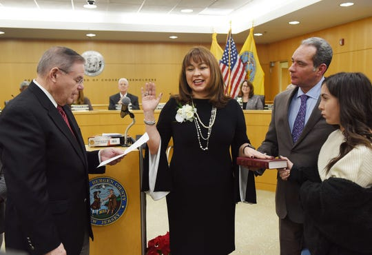 Germaine Ortiz (C) is sworn in as Chairwoman by Senator Bob Menendez as the members of her family looks on during the annual Bergen County freeholder board's reorganization meeting at Bergen County Plaza in Hackensack on 01/07/19.