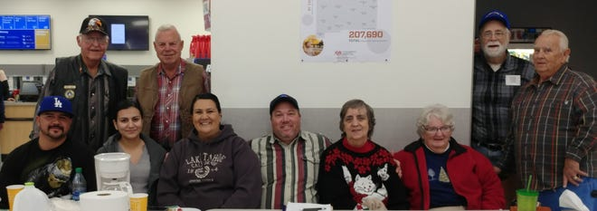 Standing, from left, Robert Baker, David Fischer, Phillip Sands and George Saylor; and seated from left,  Jamie Martiinez, Kim Ramirez, Debbie Hamilton, Coordinator Jason Hamilton, Beverly Sands, and Nancy Saylor, are just a few of the workers assisting the children with their shopping spree.