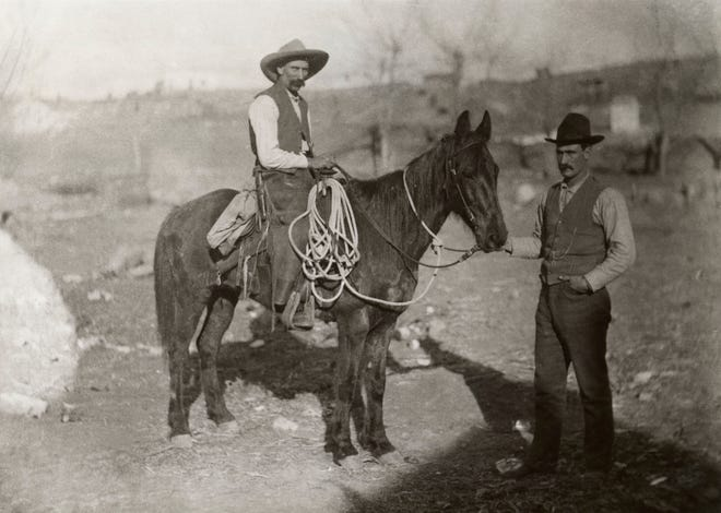 Gideon Lyda (seated) foreman, and D.C. McMillen (standing) owner, A.T. Cross Cattle Co., Grant Co. NM (circa 1900) Silver City Museum Collection