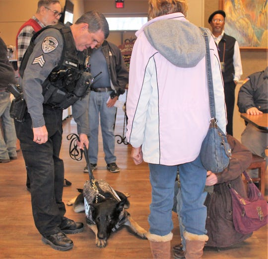 K-9 Sgt. Chris Hughs and K-9 Officer Covi, a two-year-old German Shepherd greet people at Coffee with a Cop Tuesday morning.