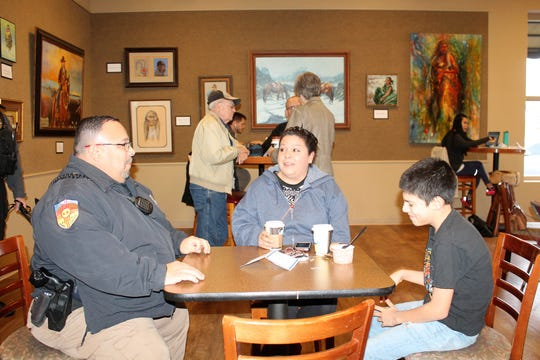 Amber Cuellar, center, and Derrick Espinoza, right, talk about an issue in their neighborhood with Alamogordo Animal Control Officer Dwain Martinez at Coffee with a Cop.