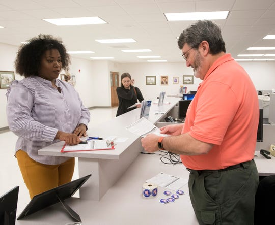 Pensacola resident Tranassa White registers to vote Tuesday with help from David Stevens, an employees of the Escambia County Supervisor of Elections Office. White is one of the estimated 1.4 million Floridians who automatically regained the right to vote when Amendment 4 went into effect Tuesday. The amendment restores the voting rights for many people with felony convictions.