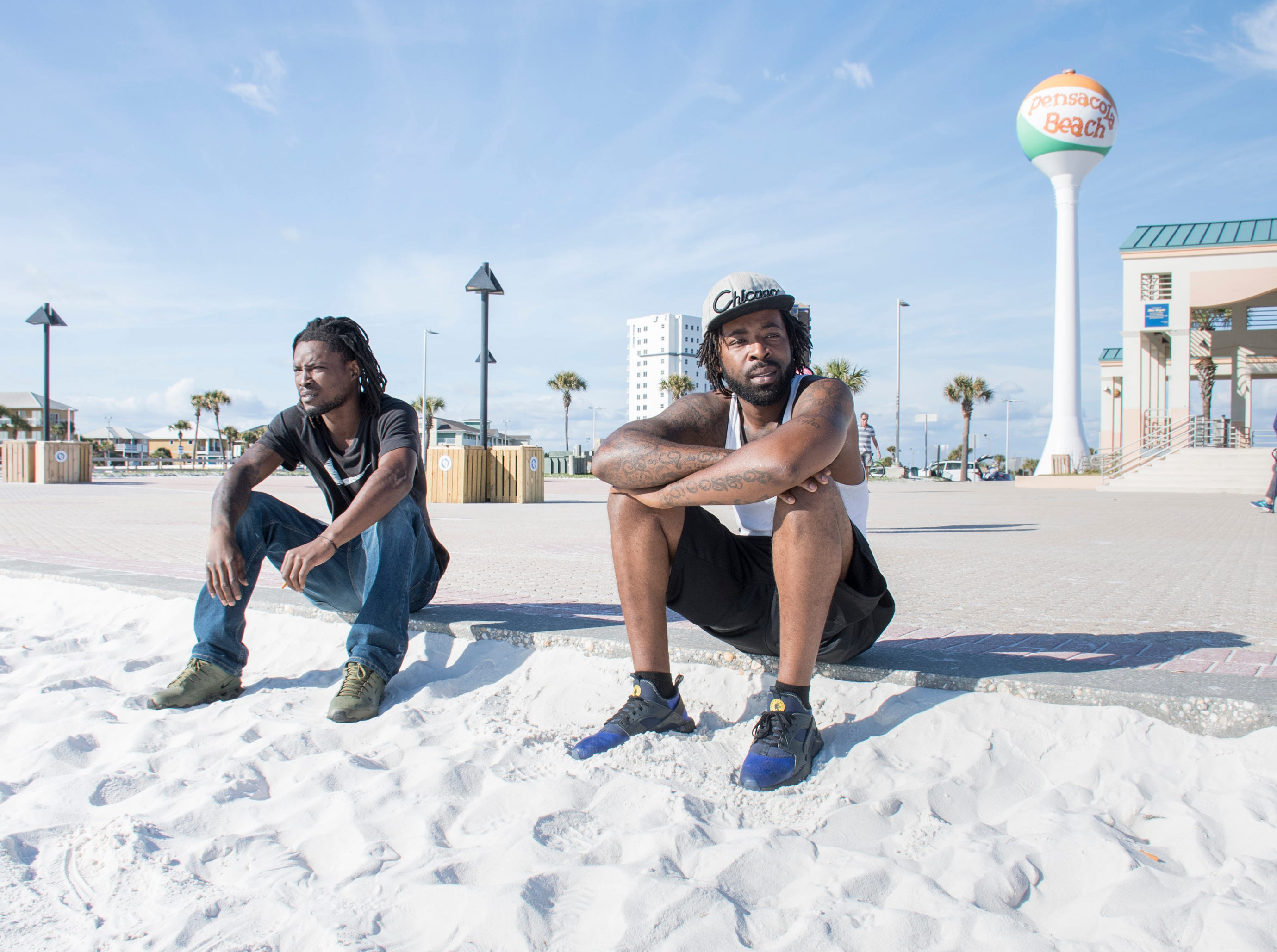 La-Mikal Kyles, left, holds his cigarette butt for later disposal as he and Charles Kyles, of Century, Florida, sit along the edge of the sand at Casino Beach in Pensacola on Tuesday, January 8, 2019.  The Florida Legislature is proposing a bill that would ban smoking on all beaches in the state.