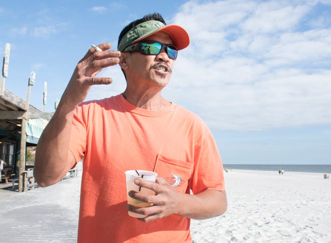 Reggy Gutierrez talks Tuesday at Pensacola Beach about his thoughts on a bill that would ban smoking at Florida beaches.