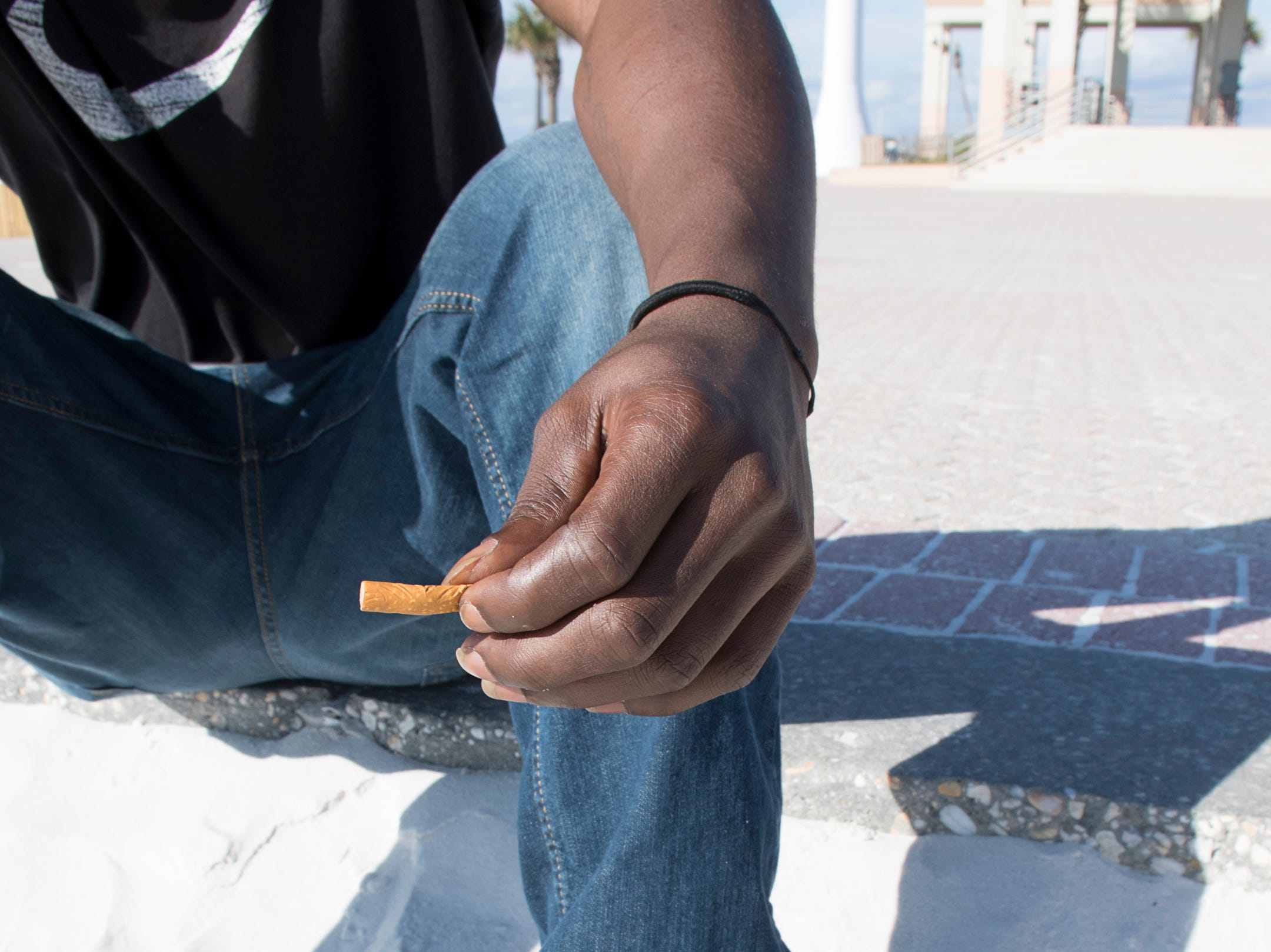 La-Mikal Kyles, of Century, Florida, holds his cigarette butt for later disposal as he sits along the edge of the sand at Casino Beach in Pensacola on Tuesday, January 8, 2019.  The Florida Legislature is proposing a bill that would ban smoking on all beaches in the state.