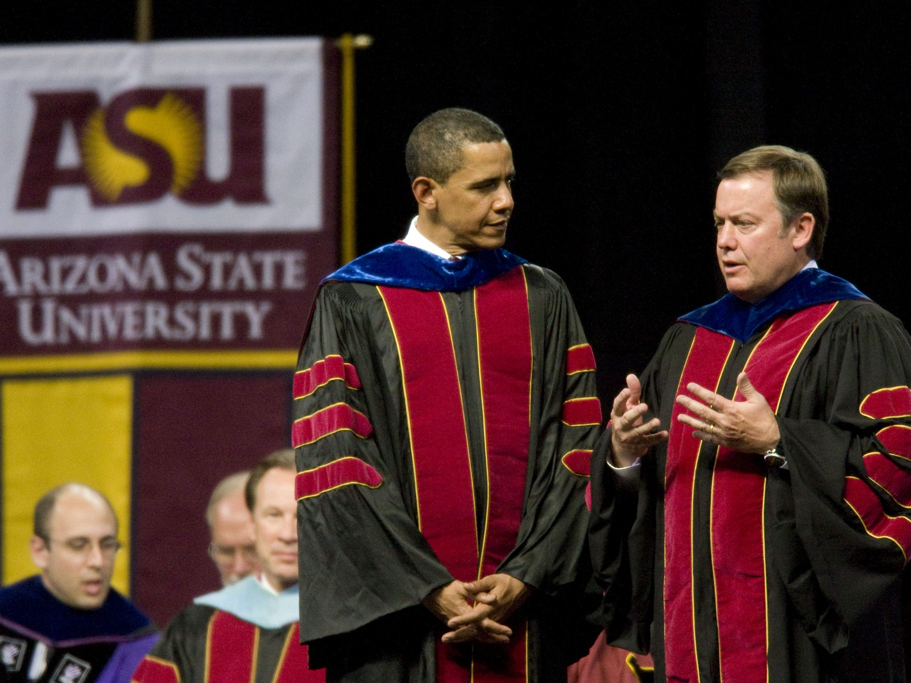 Former U.S. President Barack Obama speaks with ASU president Michael Crow during the Arizona State University commencement ceremony at Sun Devil Stadium in 2009.