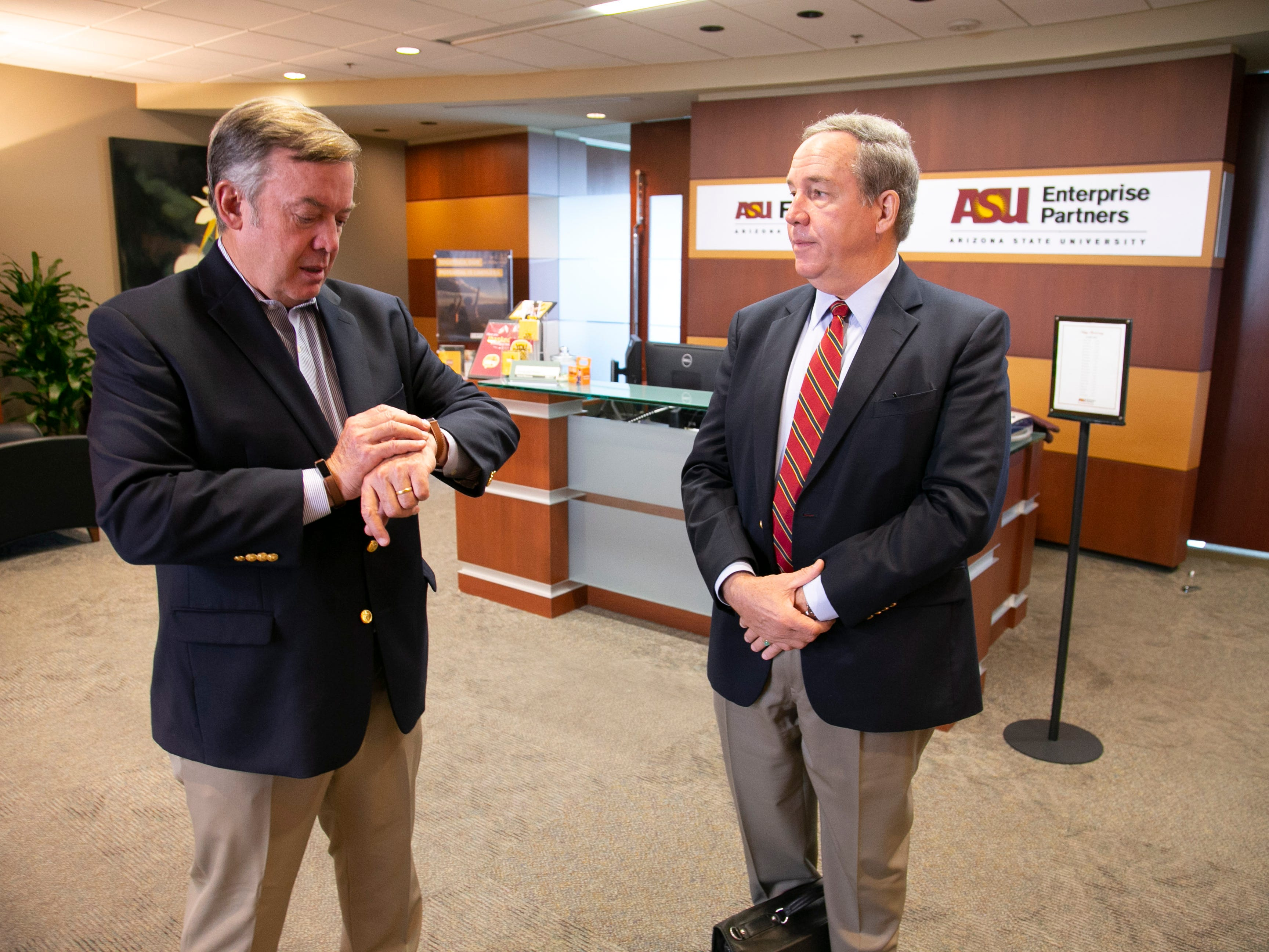 ASU President Michael Crow (left) checks his watch before heading to his next meeting. Crow also speaks with Benjamin Freakley, a retired U.S. Army general and ASU special adviser, at the Fulton Center at ASU in Tempe on Oct. 16, 2018.