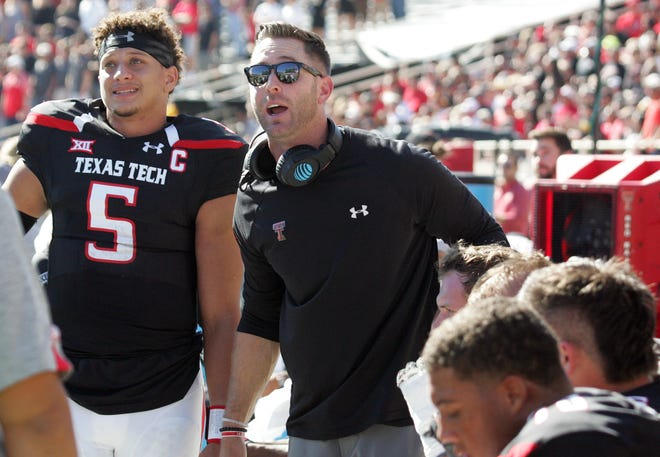 Texas Tech Red Raiders head coach Kliff Kingsbury and quarterback Patrick Mahomes (5) watch a replay on the video board during the game with the West Virginia Mountaineers at Jones AT&T Stadium.