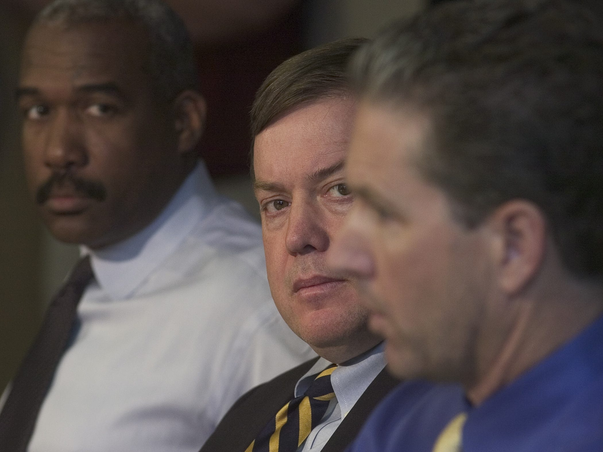 Michael Crow (center) watches as former ASU head football coach Dirk Koetter (right) answers questions about the shooting of Brandon Falkner during a 2004 press conference.