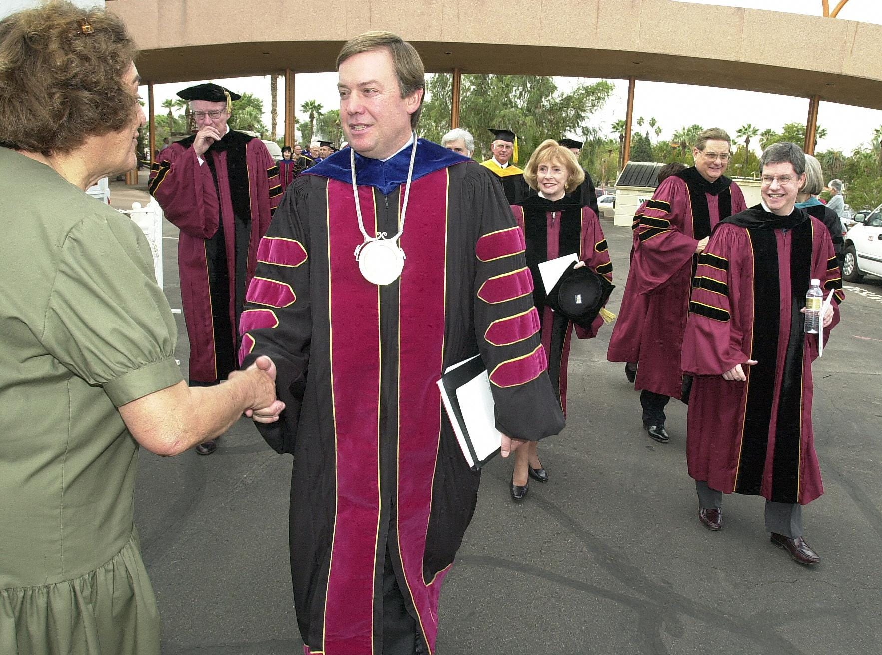 A well-wisher congratulates ASU President Michael Crow after a 2002 inauguration ceremony at the Tempe campus.