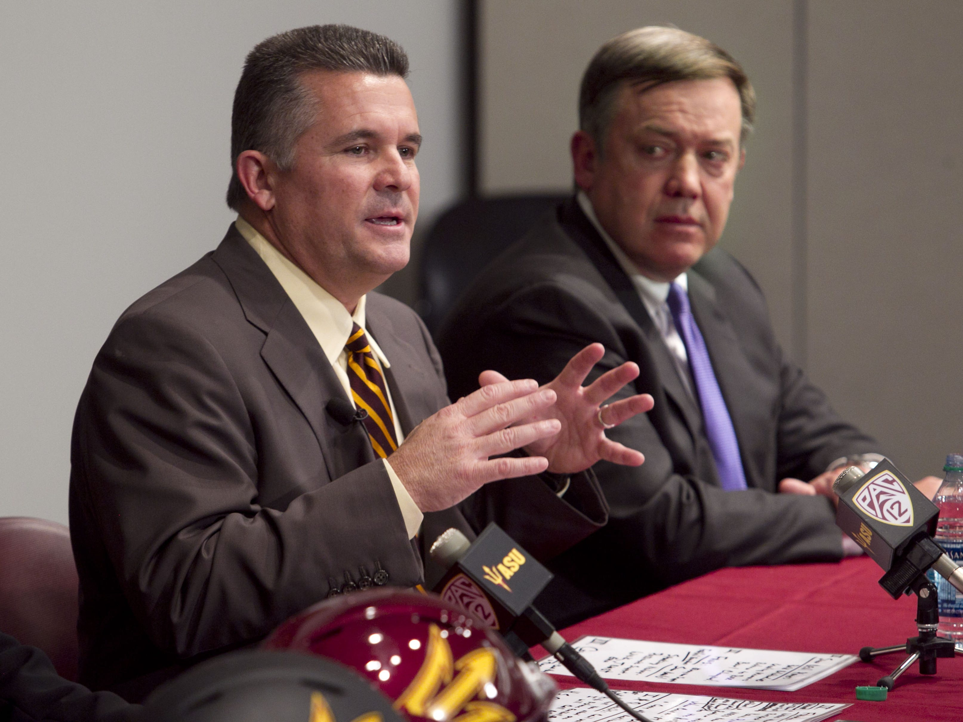 ASU President Michael Crow (right) listens as a former ASU head football coach, Todd Graham, speaks at an introductory press conference in 2011.