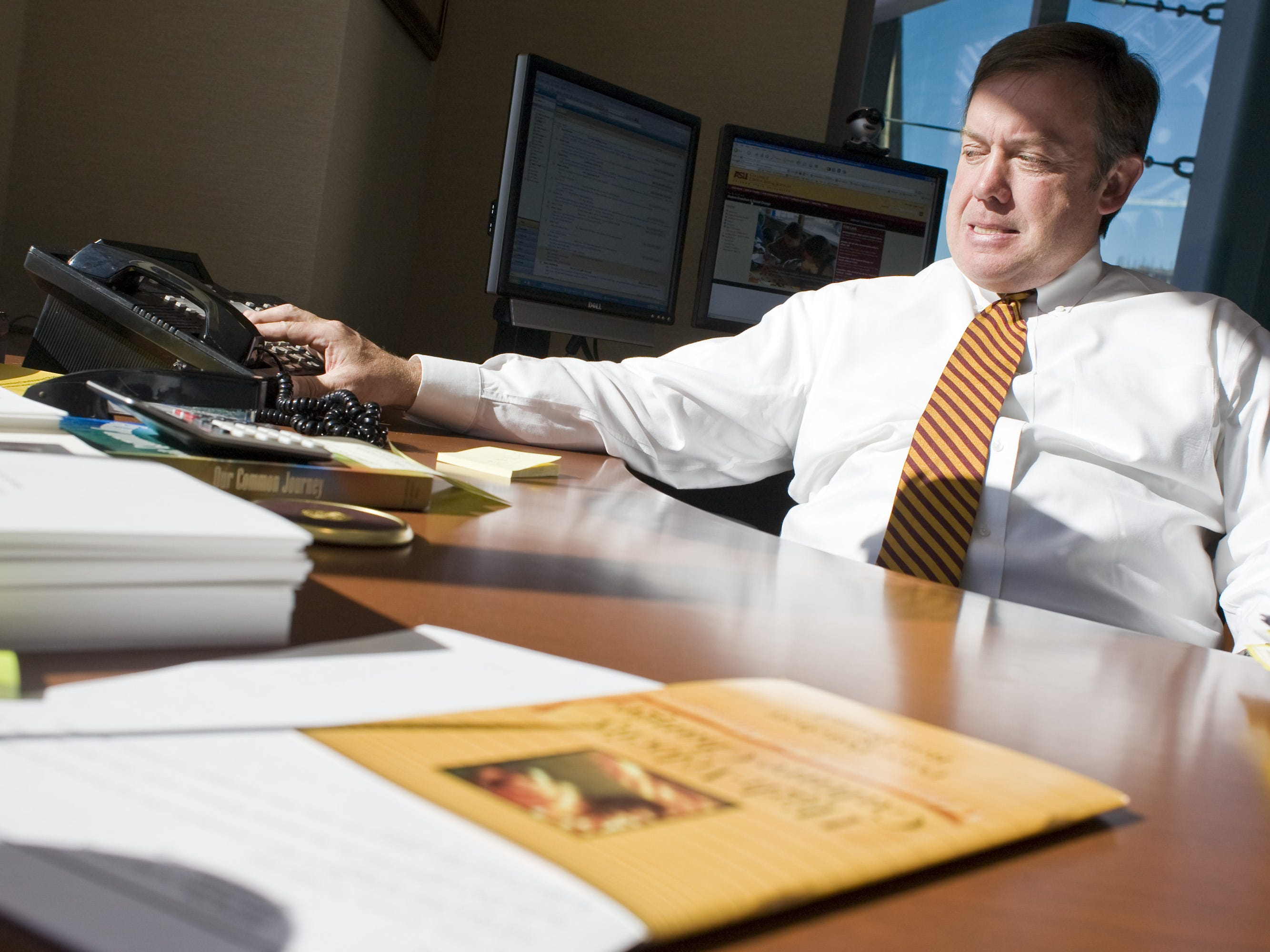 ASU President Michael Crow takes a conference call in his office in 2007.
