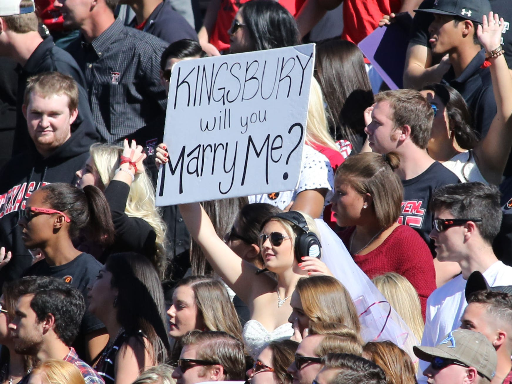 A Texas Tech fan in a wedding dress has a message for the Red Raiders head coach Kliff Kinsgbury on Oct. 31, 2015.