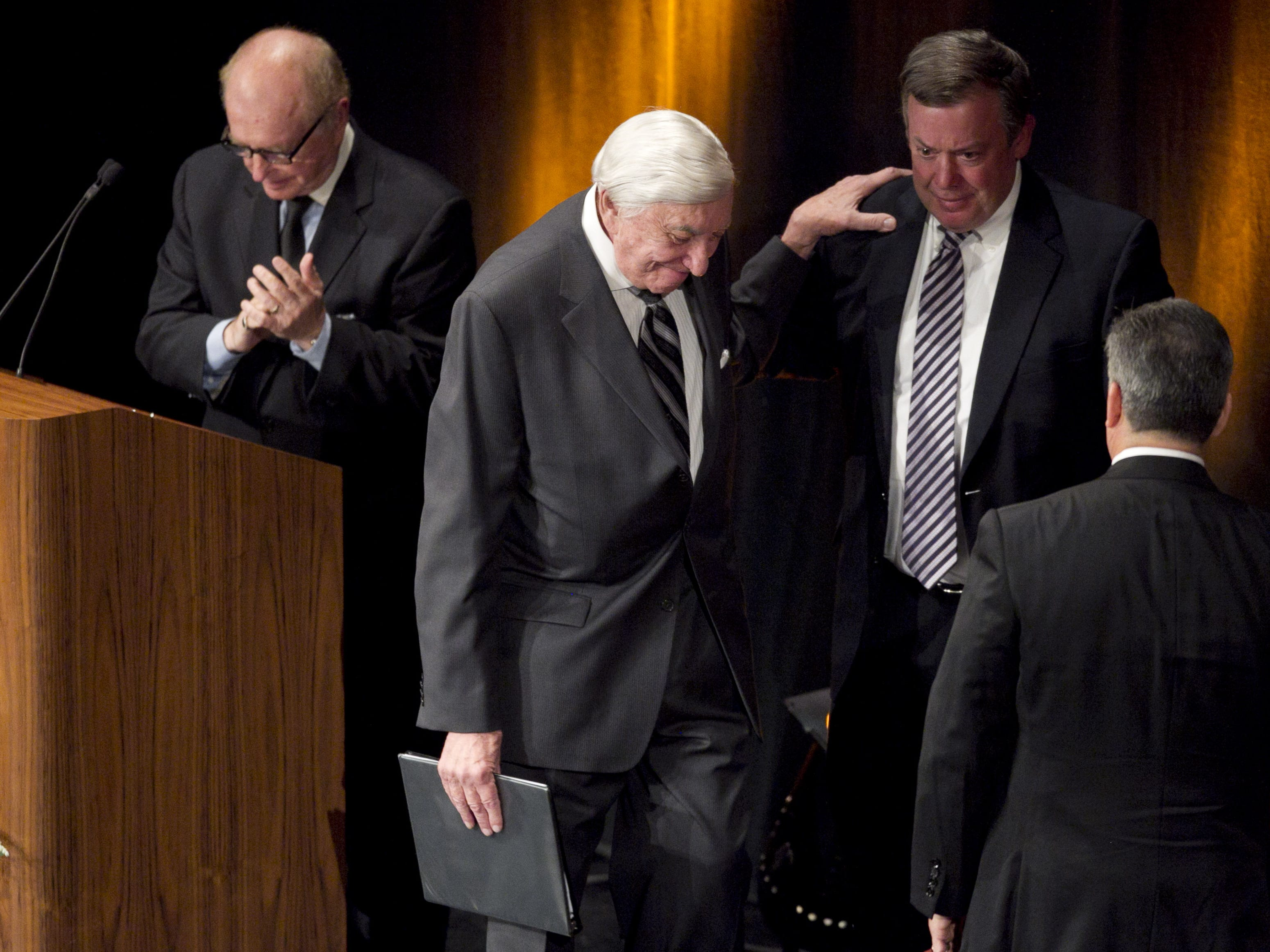 ASU president Michael Crow comforts a speaker at a 2013 memorial service for Eddie Basha, an Arizona grocery chain owner.