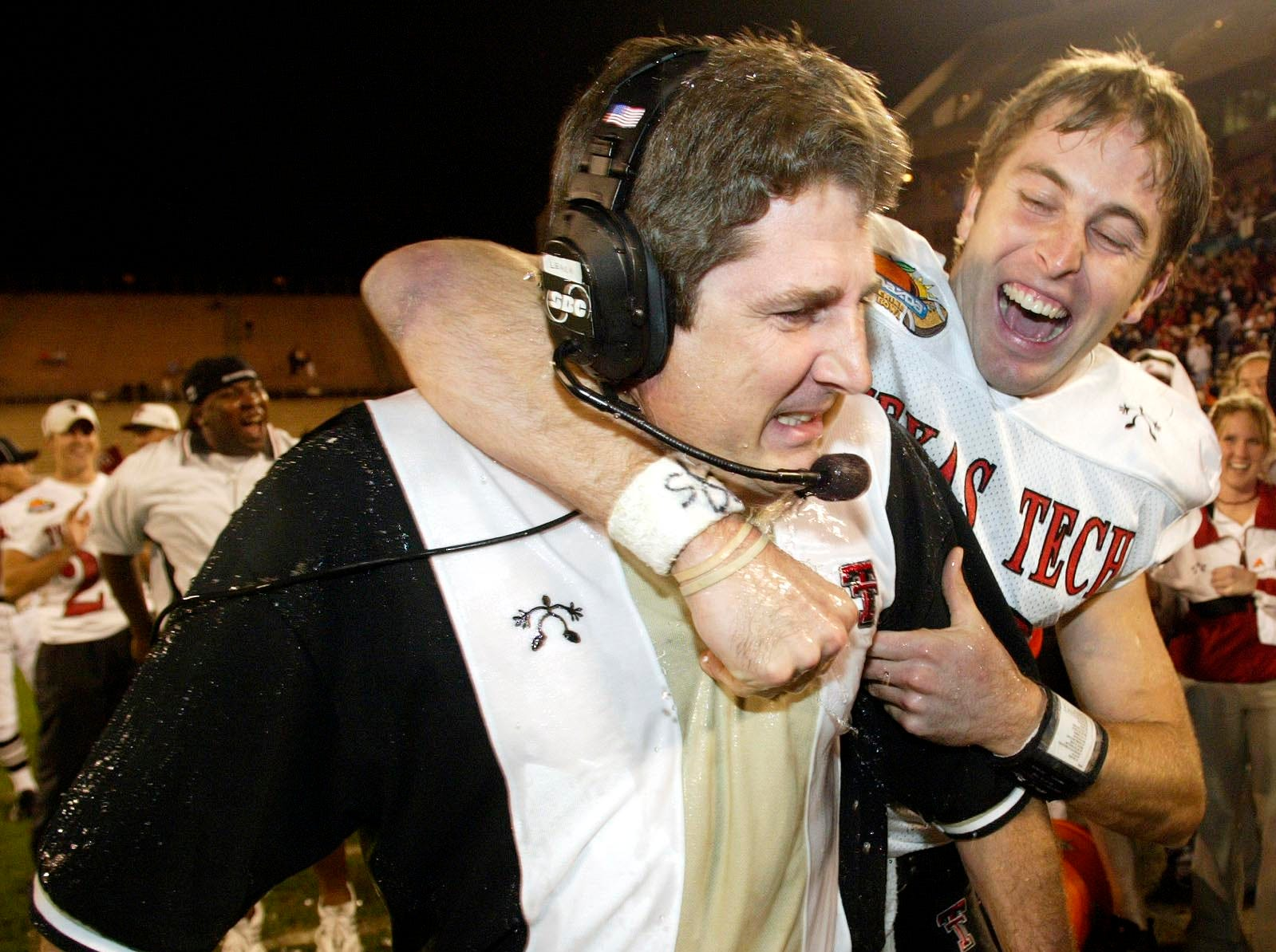 Texas Tech quarterback Kliff Kingsbury celebrates with head coach Mike Leach in the final minutes of the fourth quarter against Clemson at the Mazda Tangerine Bowl on Monday, Dec. 23, 2002, in Orlando, Fla.